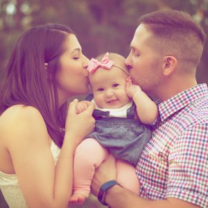 Baby girl gets kisses from parents
